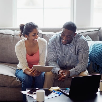 happy couple reviewing paperwork on the couch