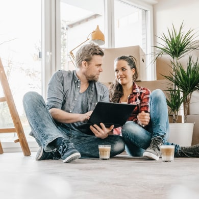 happy couple reviewing paperwork on the floor